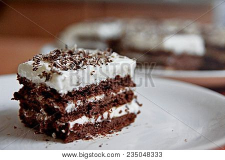 Slice of chocolate cake white cream on plate. Chocolate cake with whipped cream made for mothers day on table close up. Sweet chocolate brownie cake on background of pieces for cafe or bakery menu stock photo