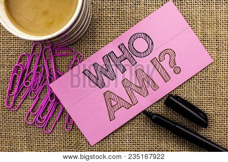 Handwriting text writing Who Am I Question. Concept meaning Question Asked Identity Thinking Doubt Psycology Mystery written Pink Sticky Note Paper the jute background Coffee Cup Pen Pins. stock photo