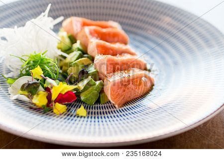 Fancy salmon tataki meal. Slices of sashimi grade salmon seared lightly to keep the fish raw inside. This is a Japanese cuisine technique which is often used in gourmet fine dining restaurants. stock photo