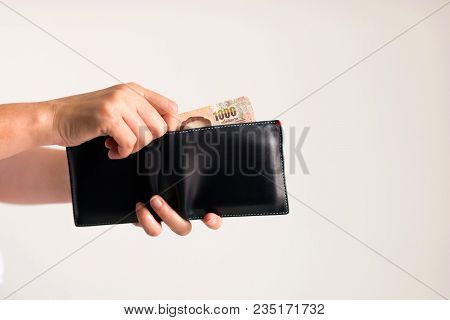 White background photo of hands holding a wallet and another hand bring Thai money from it to pay for something. stock photo