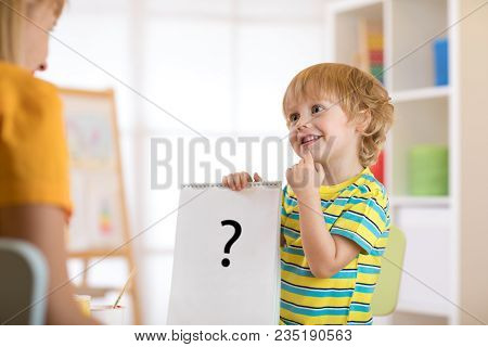 Young child boy holding drawing during therapy or lesson with woman stock photo