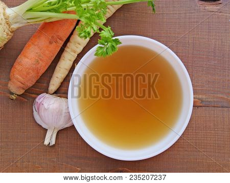 Clear beef broth, bone broth, bouillon in white bowl and vegetables on wooden table top view stock photo