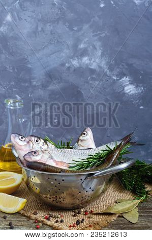 A pile of fresh raw fish with spices, lemon, rosemary on a wooden background. Fresh catch. Vertical view stock photo