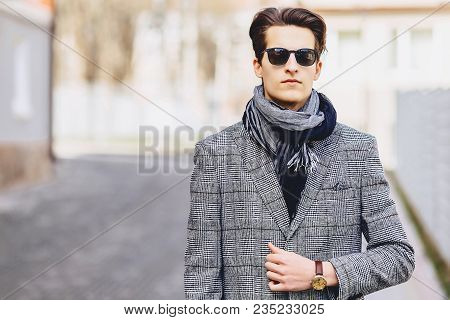 Stylish young boy in sunglasses in coat with briefcase on street stock photo