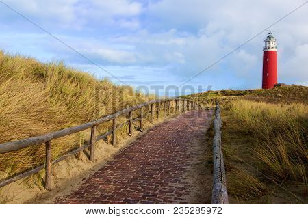 Brick Road to Lighthouse Texel on Blue Cloudy Sky background Outdoors. National Park Duinen van Texel, Texel Island, Netherlands stock photo