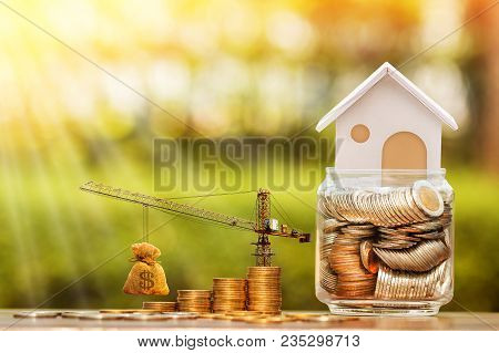 Stacking gold coins with increase and tower crane and hoist brake solutions and money bag and jar bank for build a new house, saving money and loan for construction real estate and home concept. stock photo