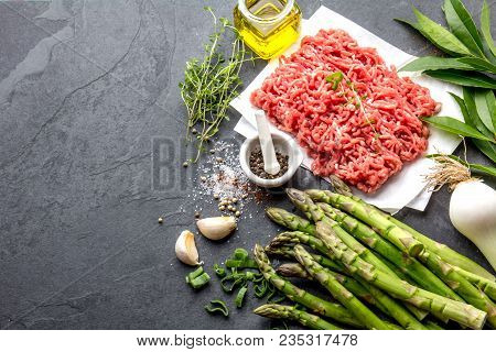 Minced beef meat and ingredients - asparagus, onion and spices. Mince and herbs. Ground meat stock photo