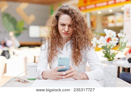Horizontal portrait of anxious discontent female model recieves message of remainder to pay bills, frowns face in displeasure, holds modern smart phone, drinks coffee in restaurant with cozy interior stock photo