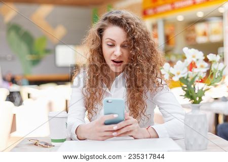 Portrait of pleasant looking young female has curly hair, wears white blouse, checks email, shocked to see many not read messages from boyfriend, has good rest in cafe alone. Technology and emotions stock photo