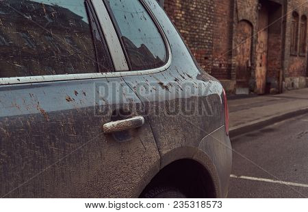Image of a dirty car after a trip off-road. Stands against a brick wall in the old part of town. stock photo