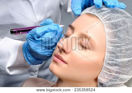Microblading eyebrows. Cosmetologist making permanent makeup. Attractive woman getting facial care and tattoo at beauty salon stock photo