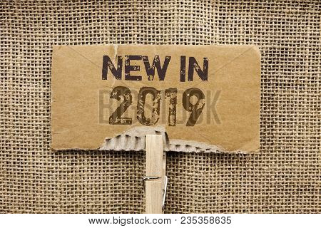 Writing note showing  New In 2019. Business photo showcasing Fresh Era Latest Year Period Season Annual Coming Modern written Cardboard Piece Holding By Clip the jute background. stock photo