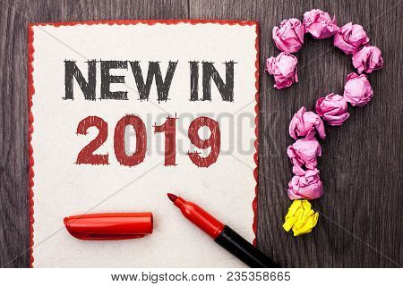 Writing note showing  New In 2019. Business photo showcasing Fresh Era Latest Year Period Season Annual Coming Modern written Cardboard Piece With Marker wooden background Question Mark. stock photo