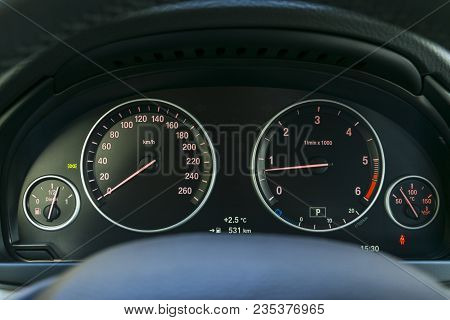 Car interior dashboard details with indication lamps. Car detailing. Car instrument panel. Dashboard closeup with visible speedometer and fuel level. Odometer, tachometer. Diesel engine. Car detailing stock photo