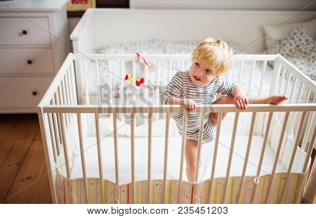 A little toddler boy getting out of a cot. Domestic accident. Dangerous situation at home. stock photo