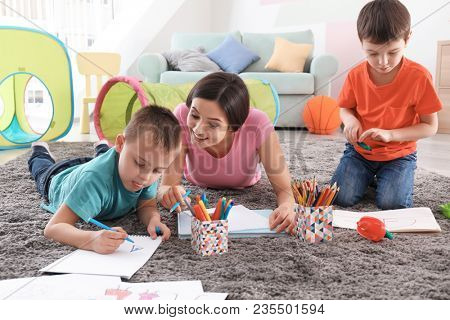 Two little boys drawing with nanny at home stock photo