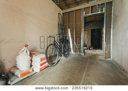 Retro bicycle and electric wires and materials, for repairs and tools, paper sacks of putty for remodeling  interior of room of house  that is under remodeling, renovation, extension, restoration, reconstruction and construction  or upgrading. stock photo