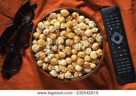Wooden bowl with sweet popcorn, TV remote control and 3D glasses on orange bedding. Top view. Snacks and food for a movie. stock photo