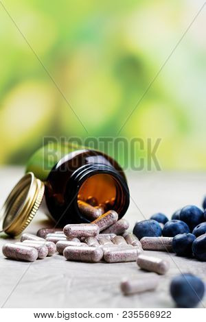 Biologically active supplement - pills for healthy eyes on green lushious background. Copy space stock photo