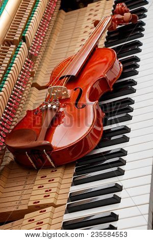 Classic Brown Violin On The Close Up Image Of Grand Piano Keys And Interior Showing Strings, Hammer