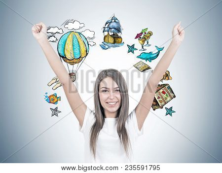 Smiling young woman with brown hair wearing a white t shirt is standing with her hands in the air and looking at the viewer. A gray wall with a travel sketch stock photo