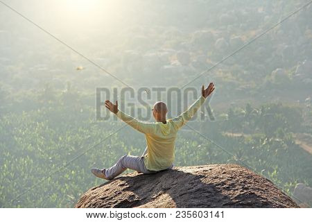 A young bald man raised his hands and greeted the sun on the top of the mountain against the background of sunrise or sunset. Relax, rest, alone with nature. Vijayanagar, karnataka, unesco. stock photo