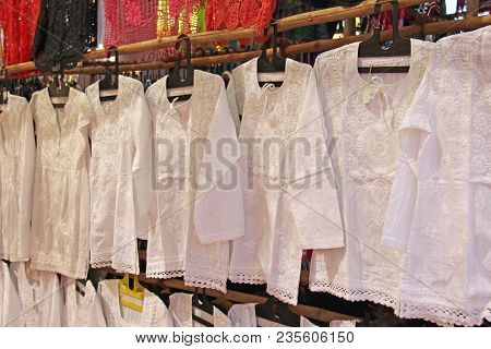 White cotton shirts with embroidery hang on hangers and are sold at the market bazaar in India, Anjuna. stock photo