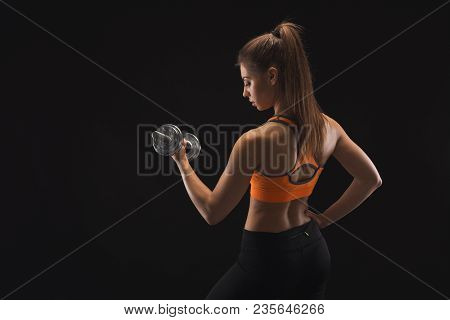 Athletic young woman with dumbbell on a black background. Studio shot, low key, copy space. Bodybuilding concept stock photo