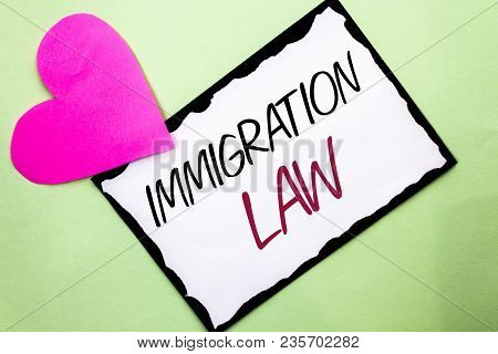 Handwriting text writing Immigration Law. Concept meaning National Regulations for immigrants Deportation rules written White Sticky Note Paper Plain background with Heart next to it. stock photo