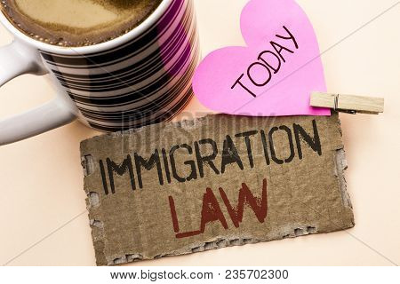 Text sign showing Immigration Law. Conceptual photo National Regulations for immigrants Deportation rules written Tear Cardboard Piece the plain background Pink Heart and Coffee Cup. stock photo