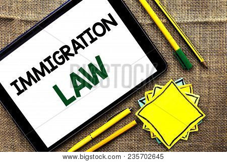 Text sign showing Immigration Law. Conceptual photo National Regulations for immigrants Deportation rules written Tablet the jute background Pens Pencil and Sticky Note Papers stock photo