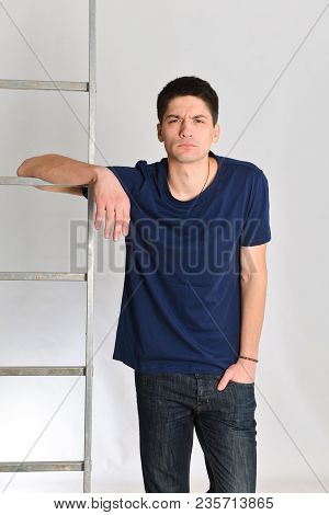 bewildered young man posing next to the ladder. repair, design, constructor stock photo