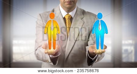 Unrecognizable recruitment agent is comparing two male candidate icons in the open palms of his hands held on same level. HR concept for equal opportunity, cultural diversity, succession planning. stock photo