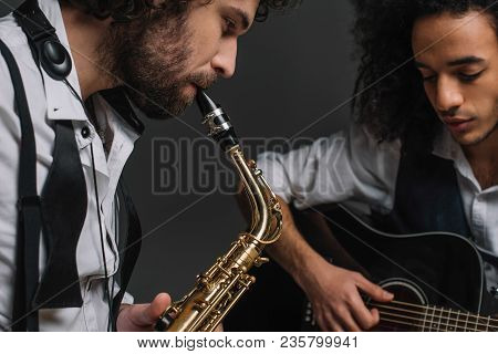 duet of jazzmen playing sax and acoustic guitar on black stock photo