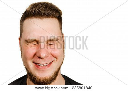 Young smiling guy with beard and modern hairstyle closing eyes on white background. stock photo
