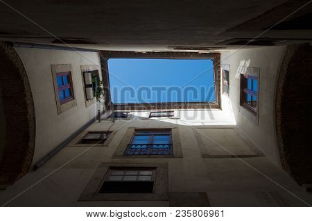 Straight up view of the blue sky from under an ancient archway. Alfama disctrict, the most famous and ancient typical neighborhood of Lisbon. Portugal. stock photo