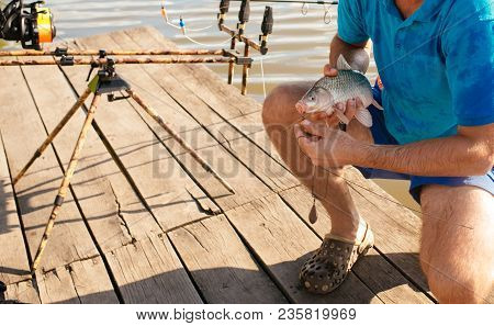 Fish hooked on mouth in male hands, bait fishing. Bait, bait fishing, fish catching. Carp, crucian carp, trout on fishhook, angling. Trophy, success, achievement. stock photo