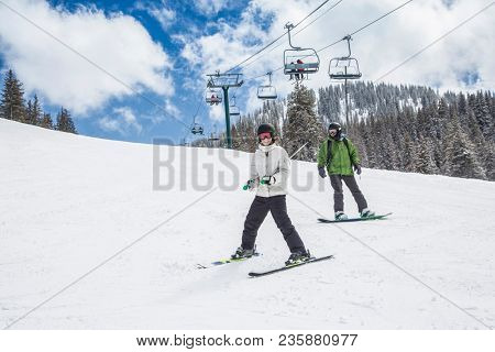 A young skier and a snowboarder skiing and boarding down a ski slope with the chair lift in the background. A fun winter day at the ski resort stock photo