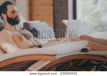 Handsome bearded Man using laptop computer while resting in spa hotel. Man relaxing after hard day at spa salon.Sunligth wooden interior.Cropped. stock photo