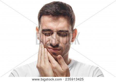 Tooth ache concept. Young man feeling pain, holding his cheek with both hands, suffering from bad toothache, having painful expression. stock photo