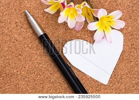 Blank note in shape of heart with copy-spce and flowers, on cork surface. stock photo