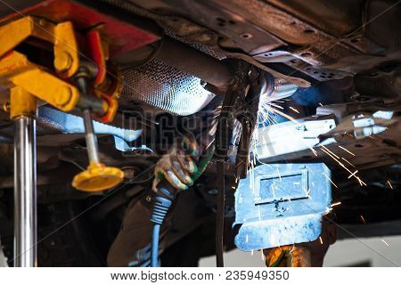 repairing of corrugation muffler of exhaust system in car workshop - welder welds the silencer on exhaust pipe by argon welding stock photo