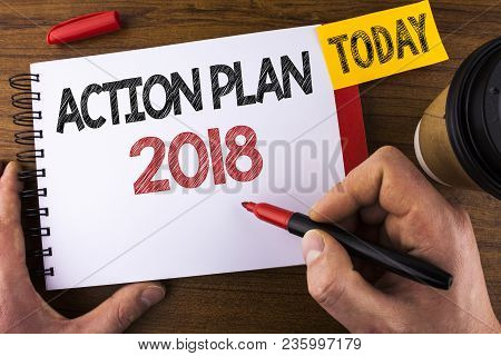 Conceptual hand writing showing Action Plan 2018. Business photo text Plans targets activities life goals improvement development written by Man Notepad holding Pen Wooden background Today Cup stock photo