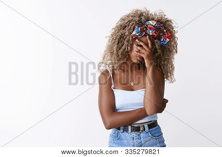 Troubled, tired, distressed african-american stylish blond curly-haired girlfriend in headband, top, facepalm, close eyes cover face with hand from fatigue, annoyed and disappointed, white background stock photo