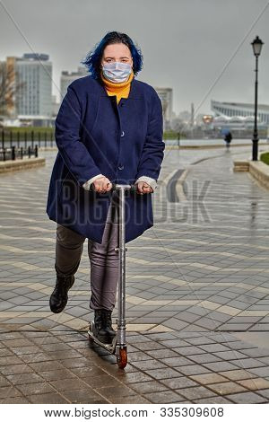 A plump young woman with a face covered with a protective medical mask riding a scooter along the river embankment in cold cloudy weather during an influenza epidemic. Girl with blue hair outdoors. stock photo