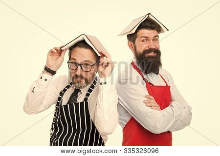 Men bearded apron reading book about culinary. Men in charge household. Some problems. Household duties. Book as roof on head. Household is boring. Who rules in house. Responsibilities of household. stock photo