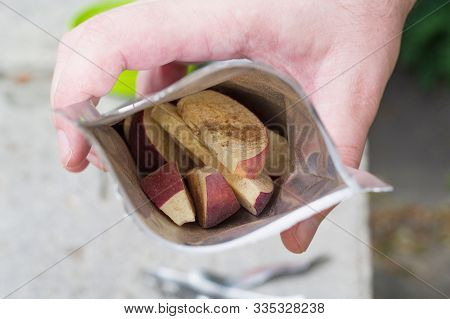 Apple sliced into slices. Apple slices per pack. Dried apples. Apple slices in a hand. stock photo