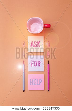 Text sign showing Ask For Help. Conceptual photo Request to support assistance needed Professional advice Coffee cup blank colored sticky note two ballpoints clips yolk background. stock photo