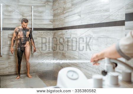 Man having high pressure shower after the mud wrapping procedure at the luxury SPA salon. Concept of hydrotherapy and Sharko shower stock photo