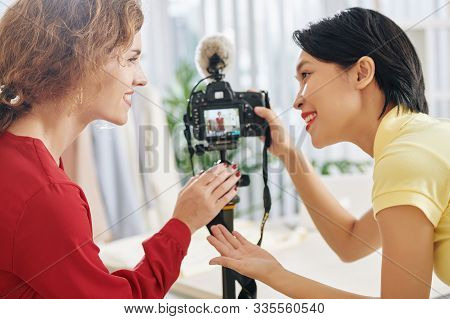 Happy beauty blogger and her assistant discussing video they filmed together for blog channel stock photo